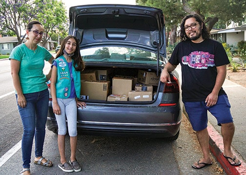 Girl Scout Troop 5604 stocks the back of their car with goods and supplies