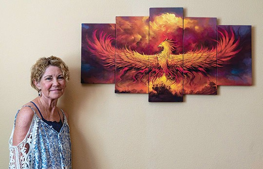 Claremont resident Terry Wilhelm stands beside a phoenix rising