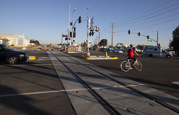 A cyclist waits for the traffic signal at the corner of Arrow Highway and E Street